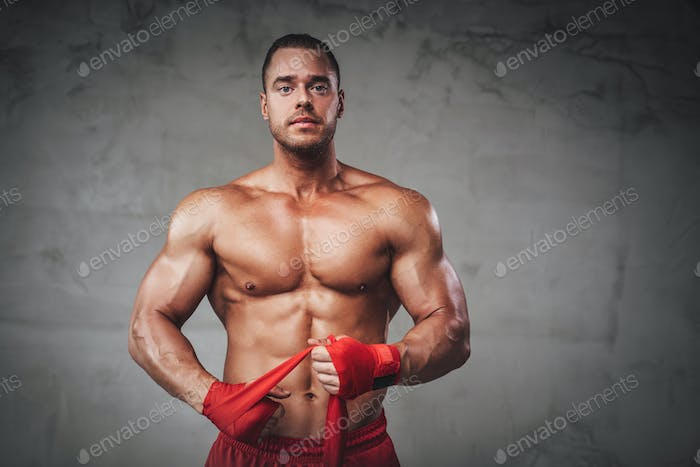 Serious guy with bandages arms posing in studio
