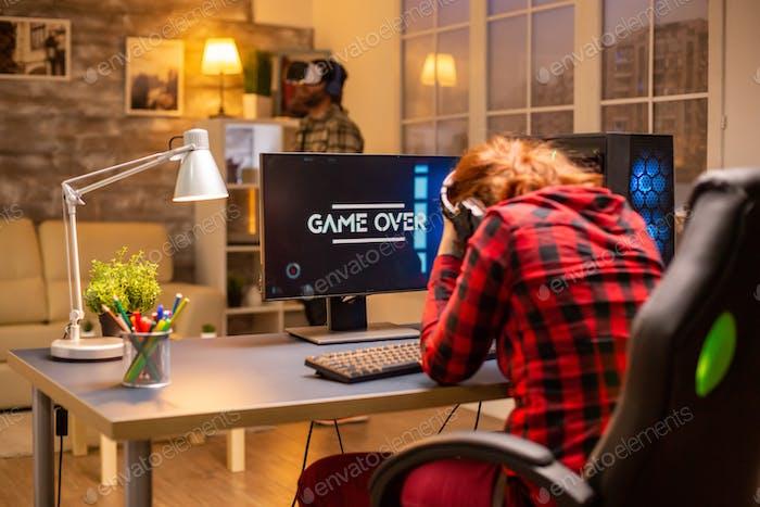 Gamer Frau verlieren bei einem Video spiel spielen spät in der Nacht im Wohnzimmer