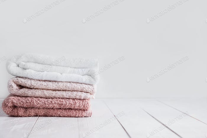 Stack of clean towels on wooden table in bathroom.