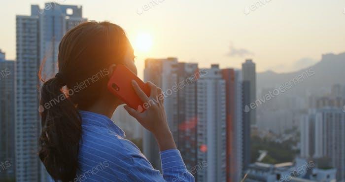 Frau sprechen mit dem Handy mit dem Hintergrund der Stadt unter Sonnenlicht