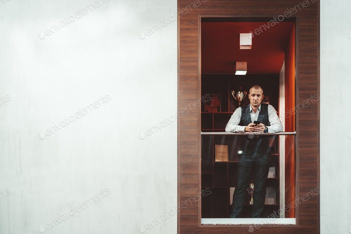Businessman with a cellphone indoors