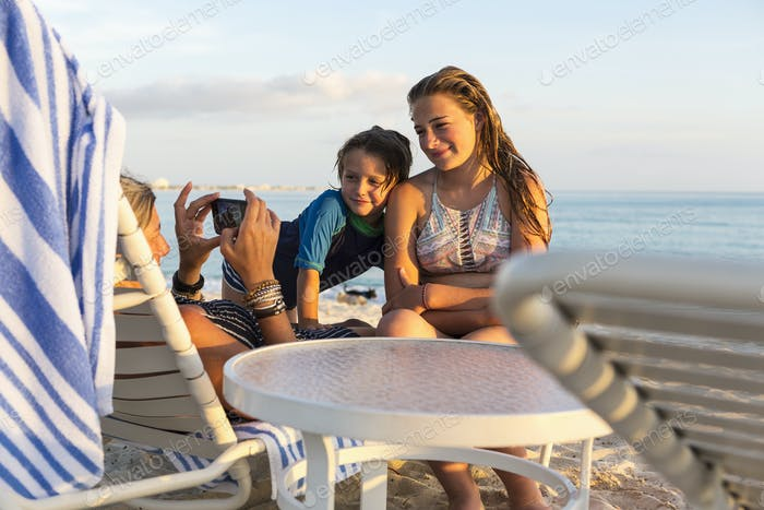mother and her children enjoying the beach at sunset, Grand Cayman Island
