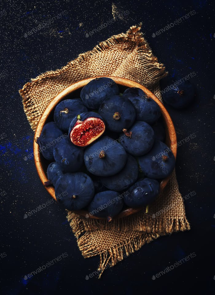 Ripe blue fresh figs in a wooden bowl