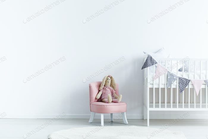 Empty wall next a to chair with a rabbit and crib with triangles