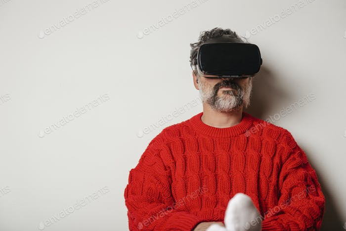 VR glasses with virtual reality seen by the man sitting at home.