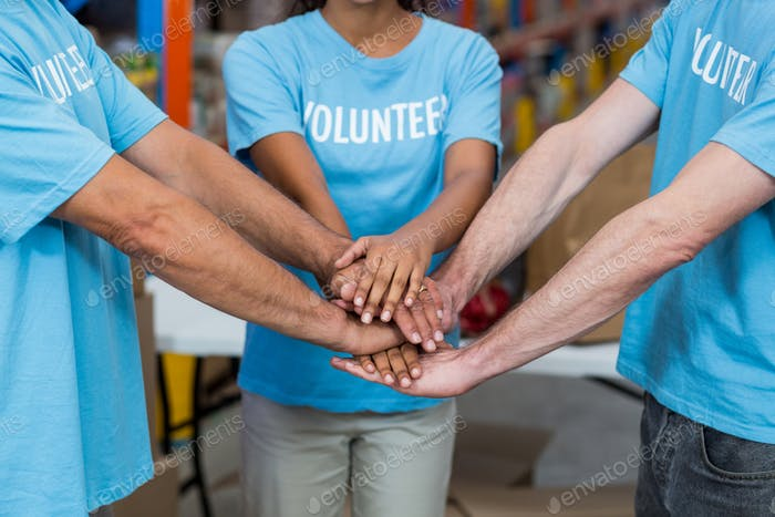 Close up of volunteers joining hands
