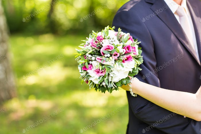 wedding couple hugging,  bride holding a bouquet of flowers, the groom embracing her