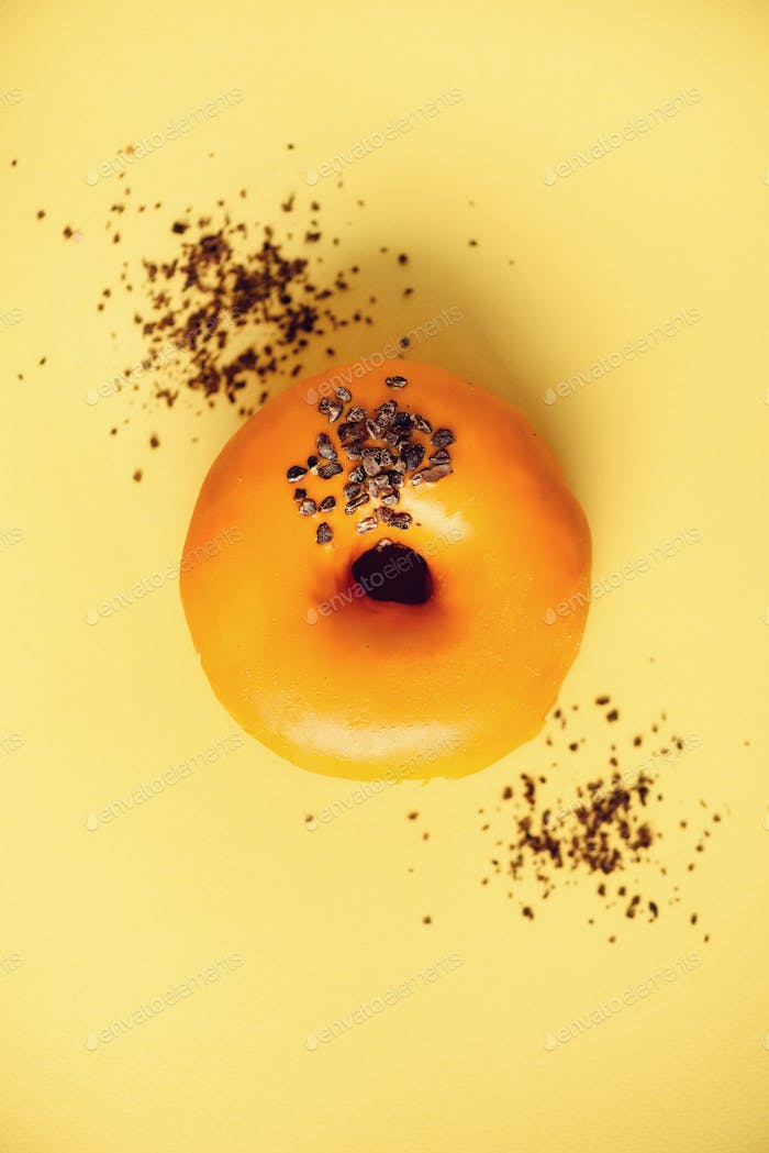 Sweet doughnut with orange glaze and chocolate on grey background. Tasty donut on pastel yellow