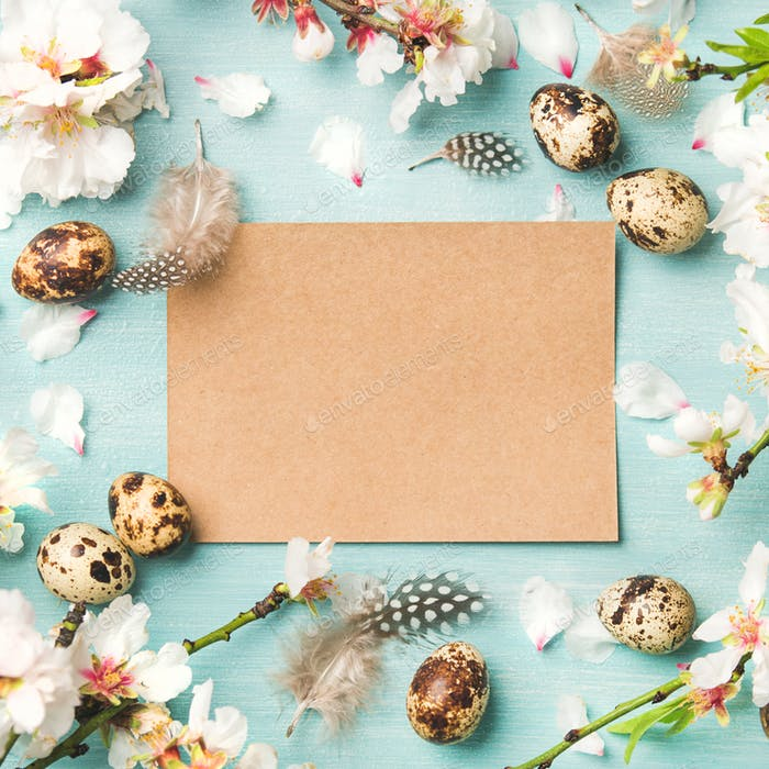 Easter background with eggs, almond flowers, paper in center