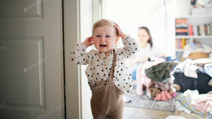 Molesto niña pequeña niño en el dormitorio en casa, llorando