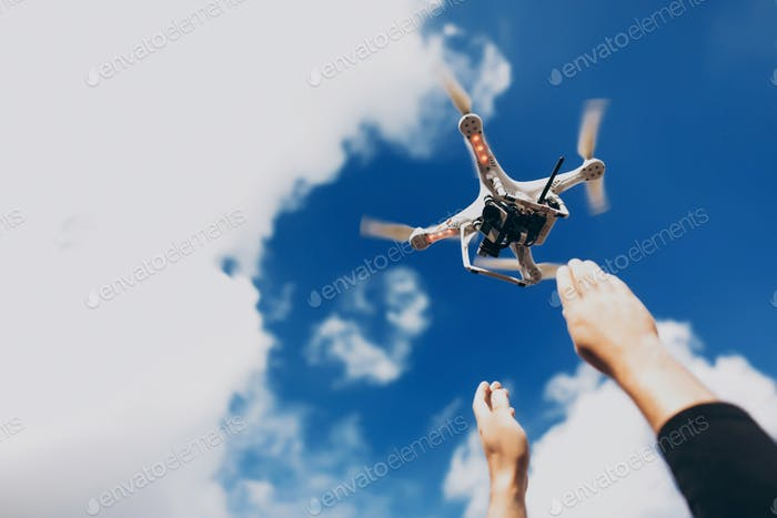 Quadcopter with camera in blue sky with clouds