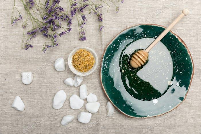 Blick von oben auf natürliche Körperpflege- und Aromatherapie-Produkte auf grauem Stoff