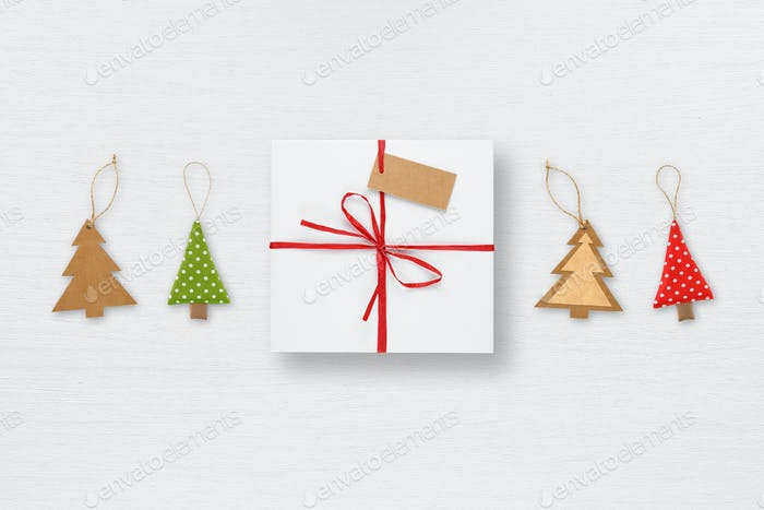 Gift box with tag and christmas tree decorations on white table top view