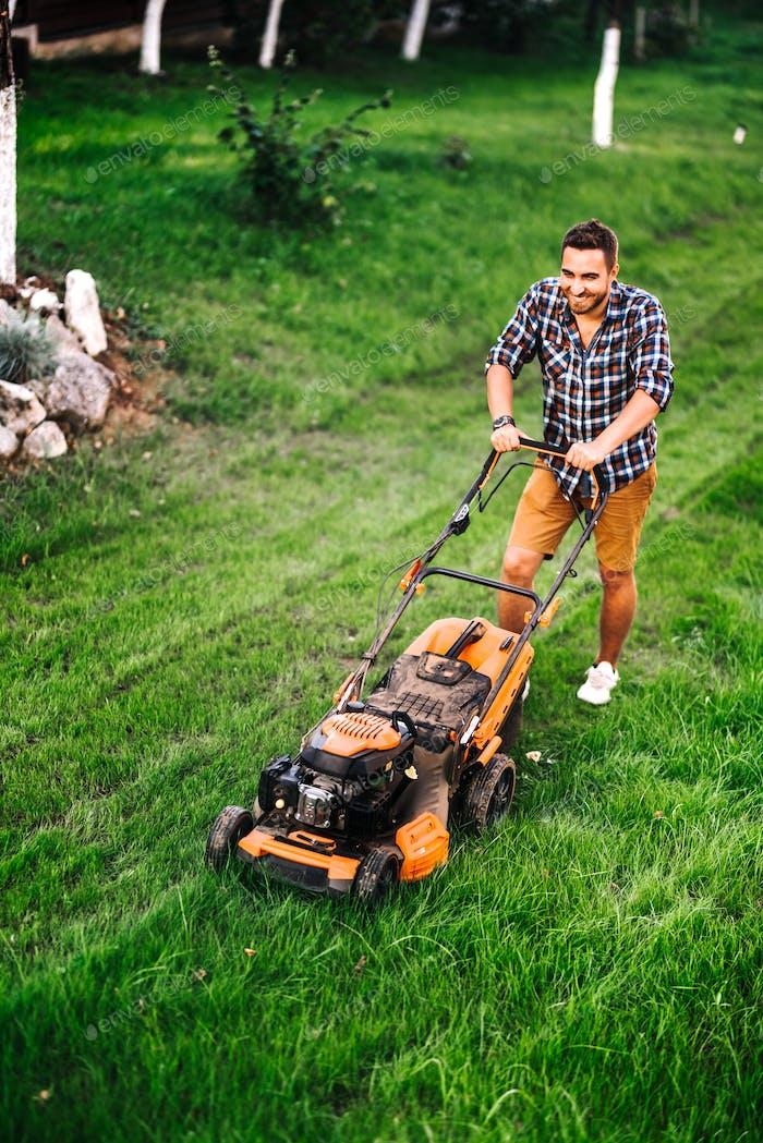 Landschaftsbau Details, Industriegärtner arbeiten mit Rasenmäher und Schneiden von Gras im Garten