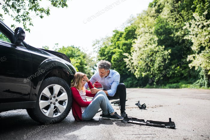 Young woman by the car after an accident and a man helping her.