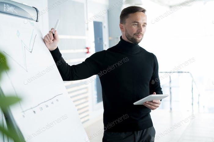 Serious business trainer explaining graph