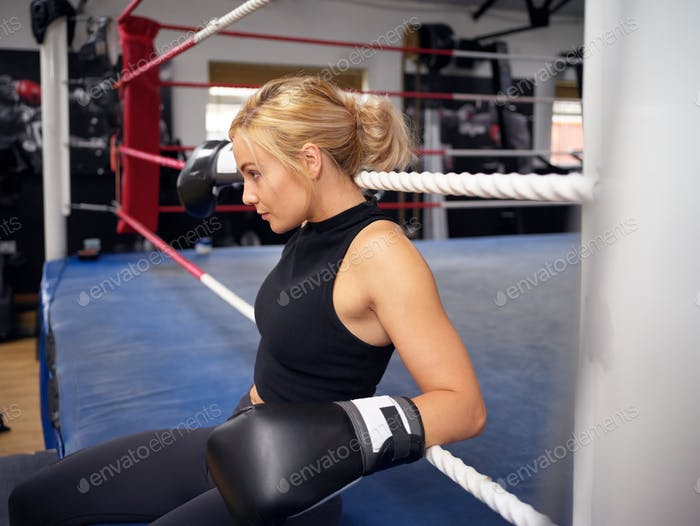 Female Boxer  Training In Gym Wearing Boxing Gloves Sitting On Boxing Ring