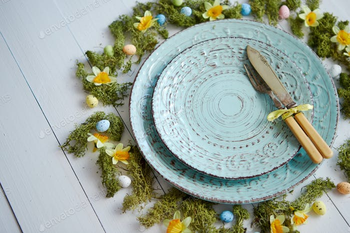 Easter table setting with flowers and eggs. Empty decorative ceramic plates
