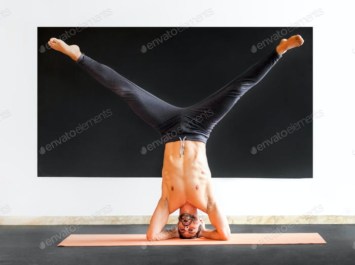 Athletic man doing a sirsasana heastand exercise