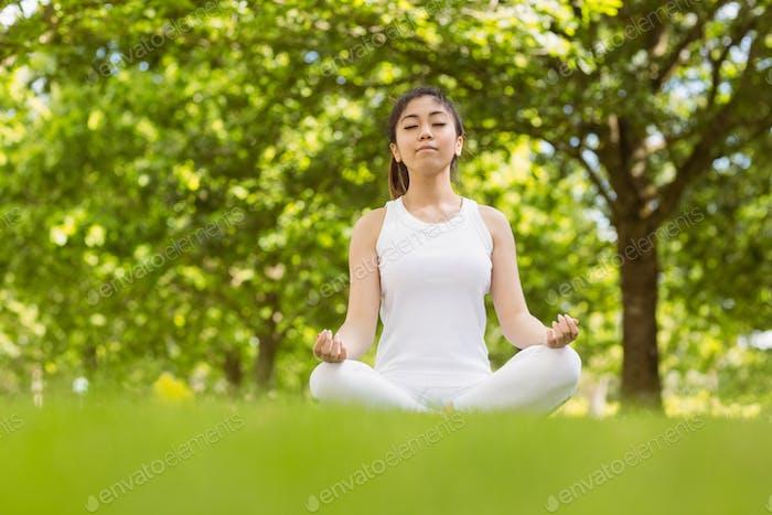 Volle Länge der gesunden und schönen jungen Frau sitzt in Lotus Pose im Park