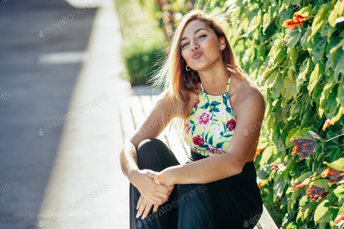 Pretty young girl sitting on urban bench blowing a kiss