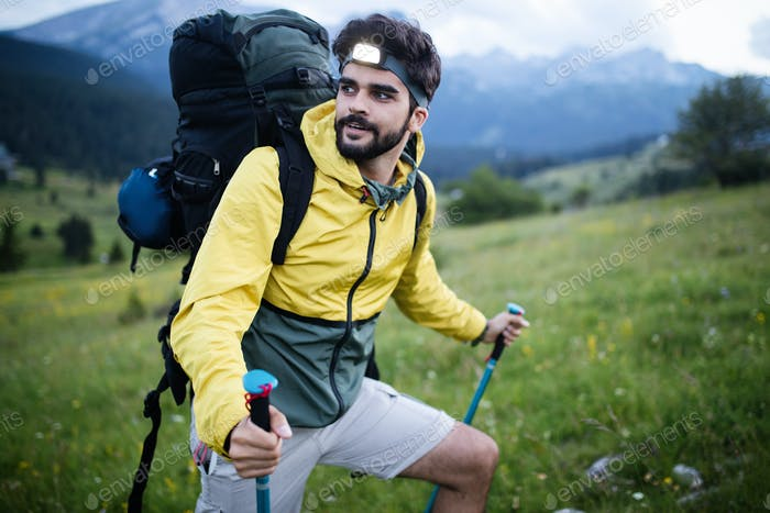 Attractive hiker with big traveling rucksack moving up on the mountain trail and smiling