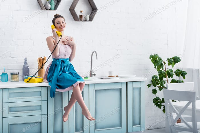 happy young woman in apron sitting on table and talking on retro yellow telephone in kitchen