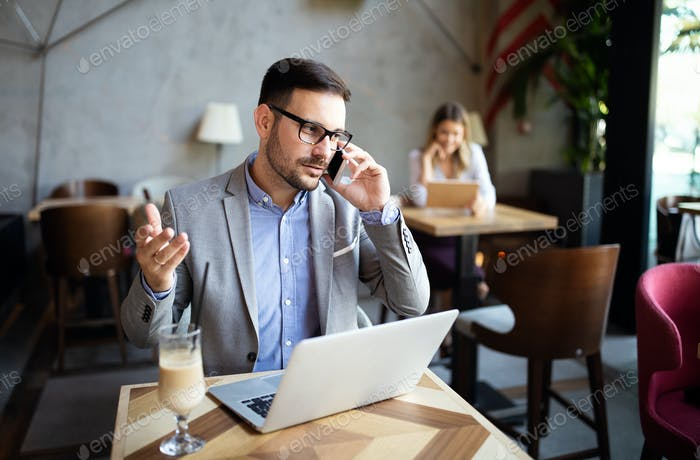 Happy confident businessman sitting with laptop at office