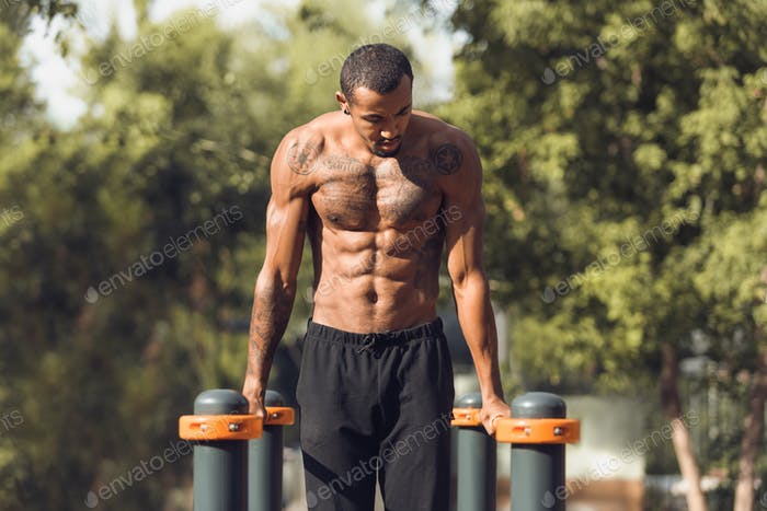 Athletic naked man doing push ups on parallel bars