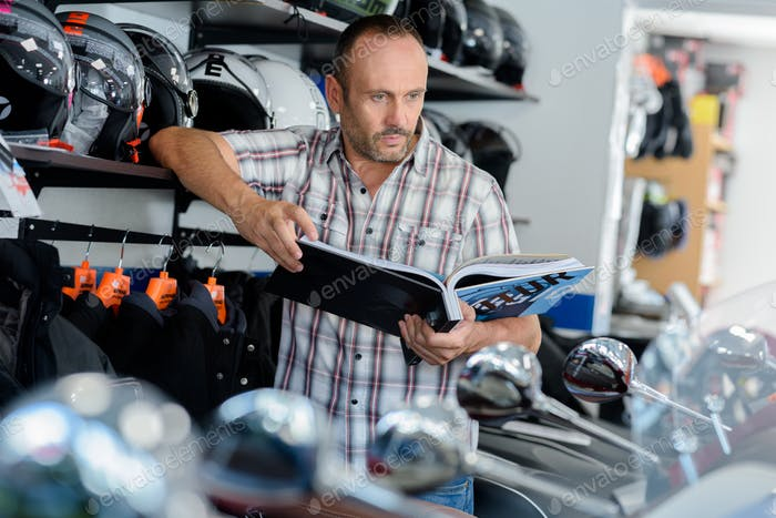 man browsing motorbike catalog