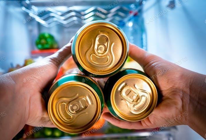 Mann nimmt Bier aus einem Kühlschrank