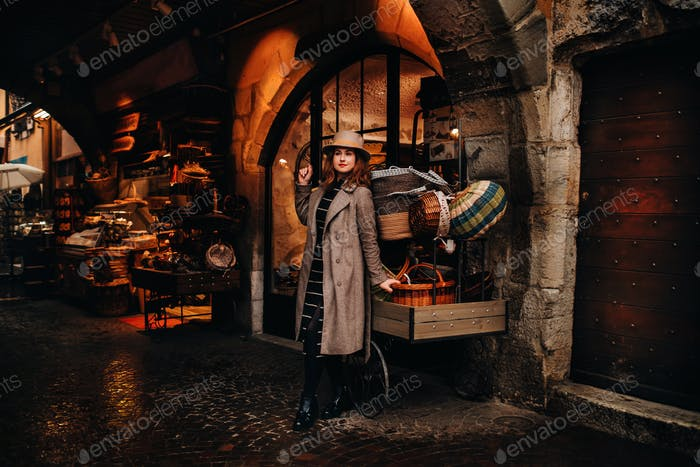 a girl in a coat and hat stands near baskets in the old town of Annecy, spending time outdoors