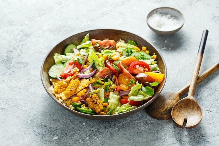 Vegetable salad with tomatoes, lettuce, cucumbers, onions and grilled corn