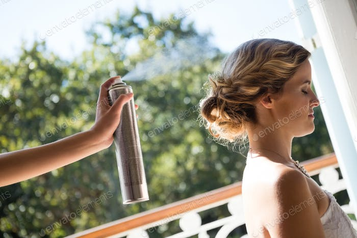 Bridesmaid applying hairspray to bride in dressing room