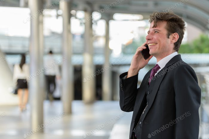 Happy thoughtful businessman smiling and talking on mobile phone