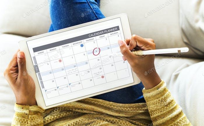 Woman checking calendar on digital tablet