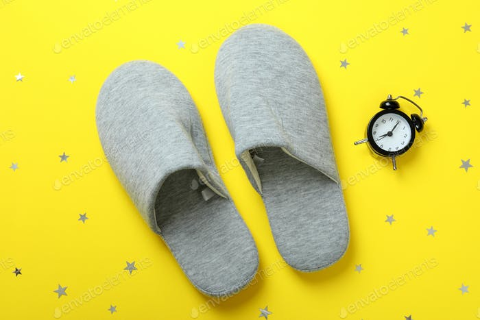 Alarm clock and slippers on yellow background