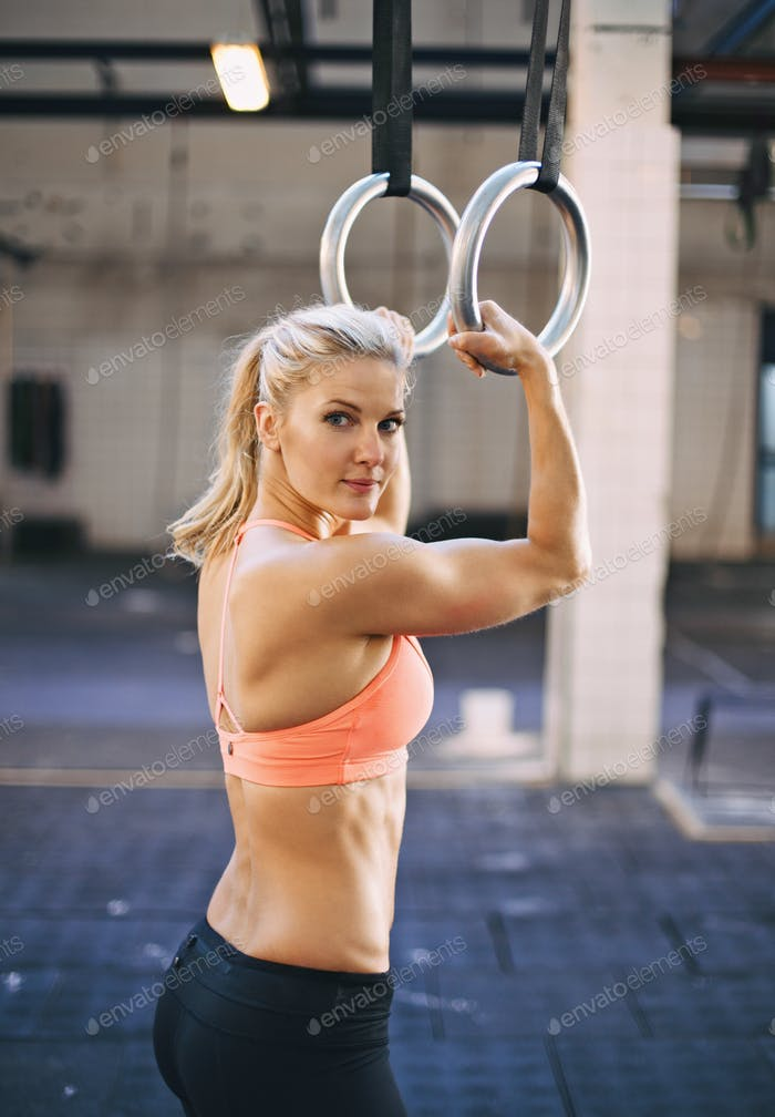 Muscular female athlete exercising with gymnast rings