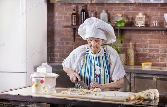 Senior woman in chef hat preparing pastries in kitchen