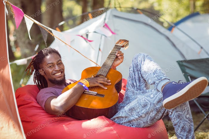 Happy hipster relaxing on campsite playing guitar at a music festival
