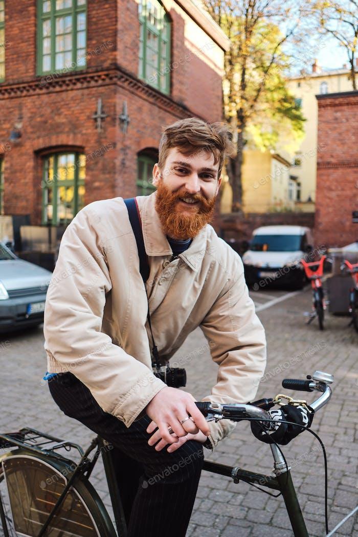 Junge positive bärtige Mann auf dem alten Fahrrad freudig suchen in der Kamera auf der Straße