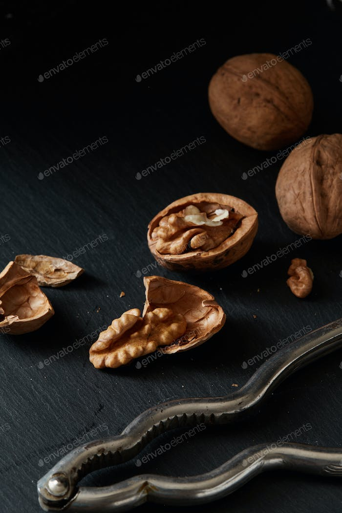 Walnuts and kernels on a black backdrop with nutcracker