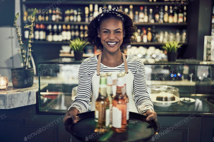 Friendly African restaurant server holding a tray of drinks