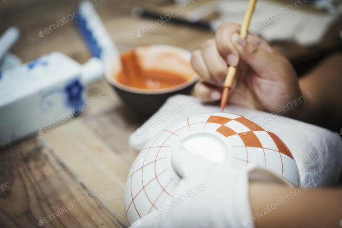 Person painting geometric pattern onto white bowls