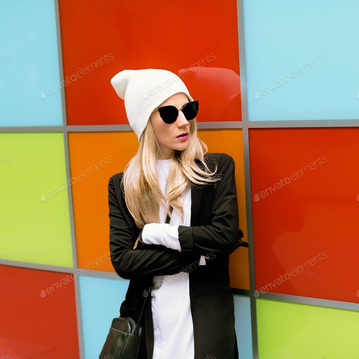 Fashionable blonde standing against a bright wall. Urban autumn