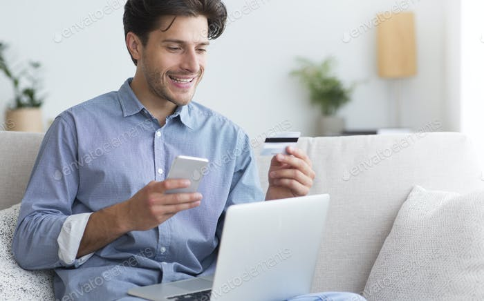 Man Holding Credit Card And Cellphone Sitting With Laptop Indoor