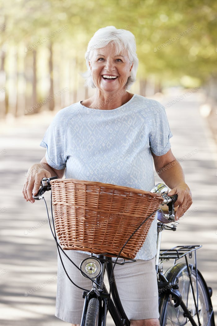 Portrait Of Smiling Senior Woman Cycling On Country Road