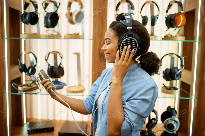 Woman listening to music in headphones store