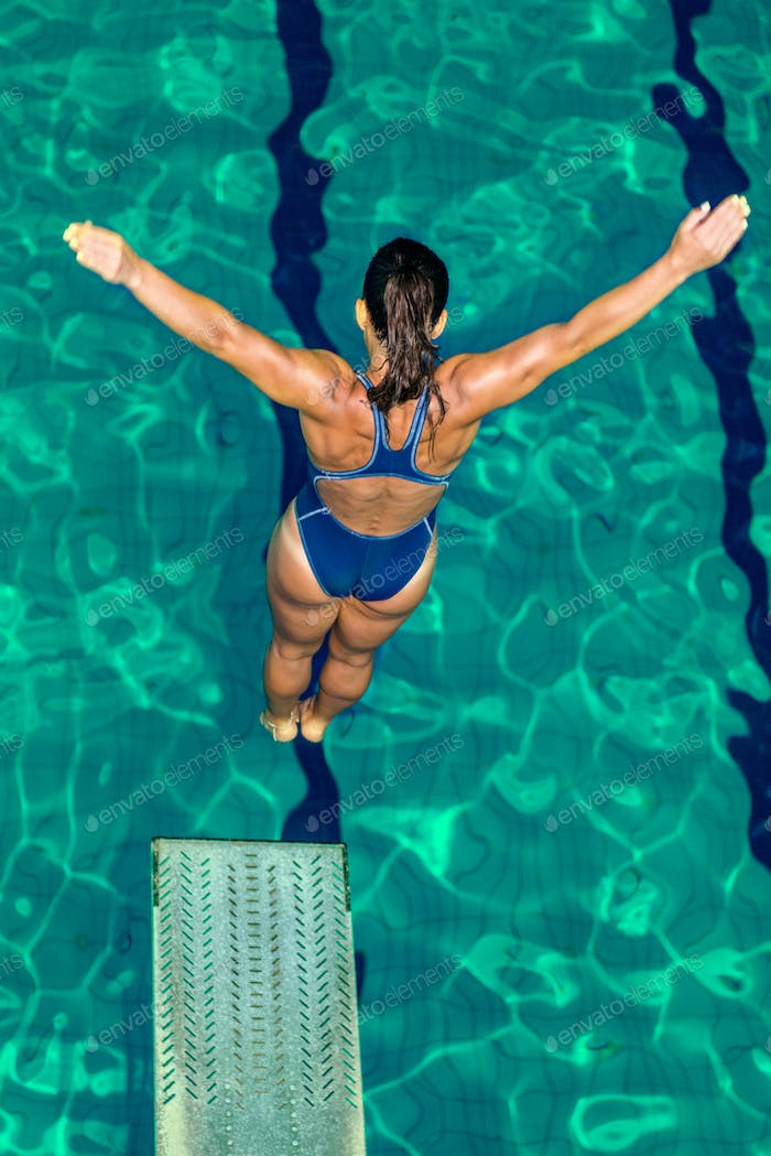 Female diver jumping into the pool