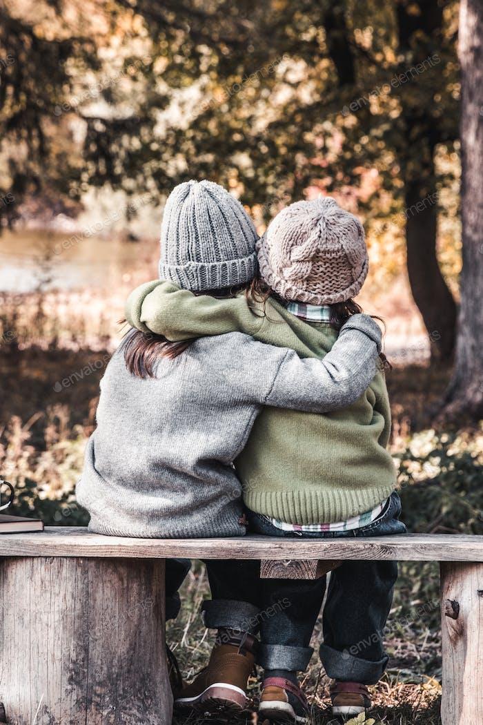 Zwei glückliche Mädchen als Freunde umarmen sich gegenseitig. Kleine Freundinnen im Park. Kinder Freundschaft